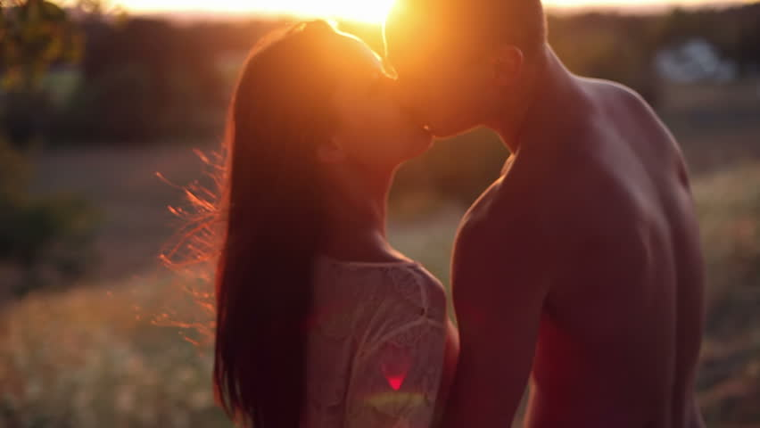 Girl takes off her shirt and kisses boy in a field during a sunset. Medium shot.