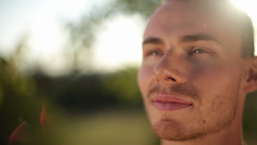 Attractive man looks at the camera and smiles. Close up shot.