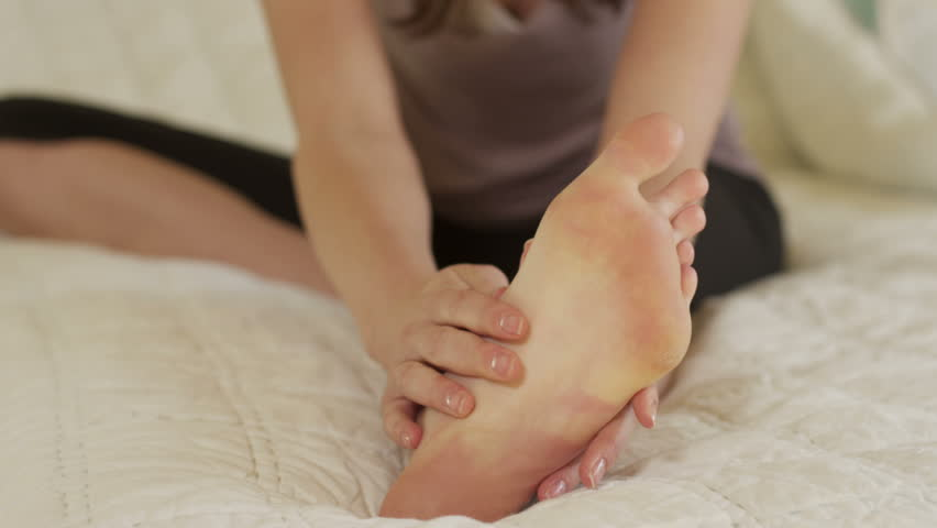 Woman with foot ache massages feet