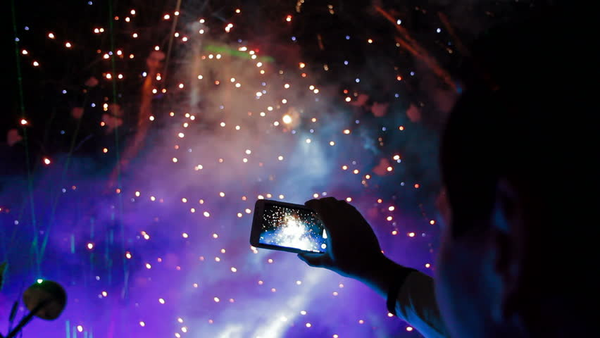Man filming colorful fireworks on his cell phone. Filming fireworks.