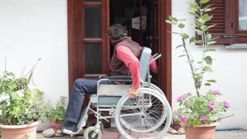 man in wheelchair goes out of his home - HD stock footage clip