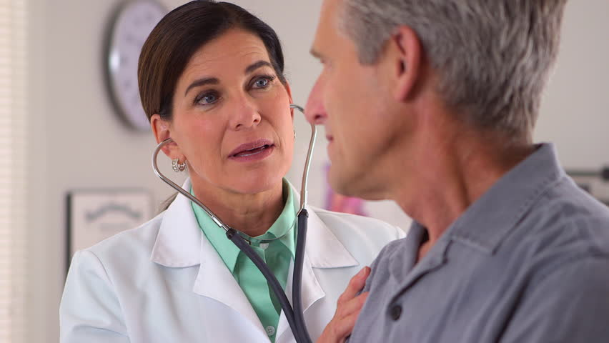 Friendly doctor listening to patient's heartbeat