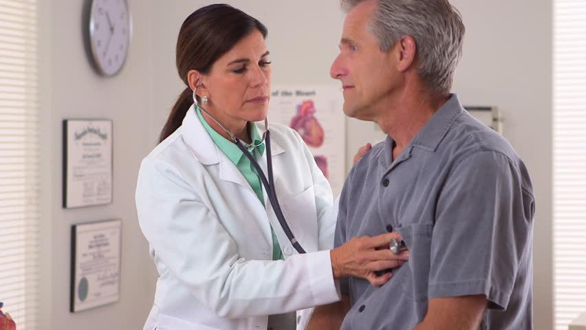 Woman doctor listening to elderly patient's heartbeat