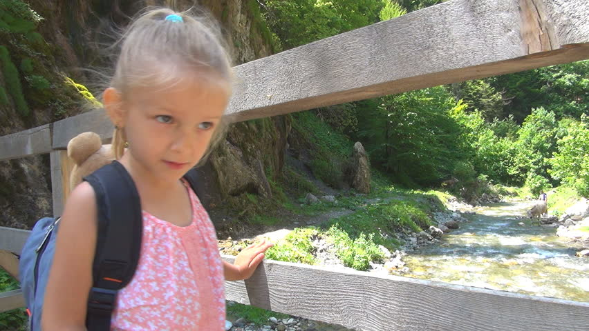 Child on a Bridge Looking to a Spring in Mountains, Tourist in a Trip, Children
