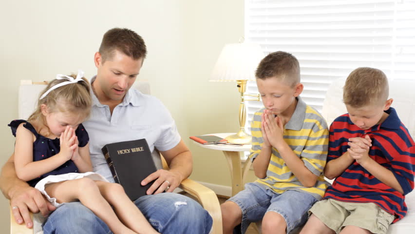 Children bow their heads in prayer while their father says a prayer.