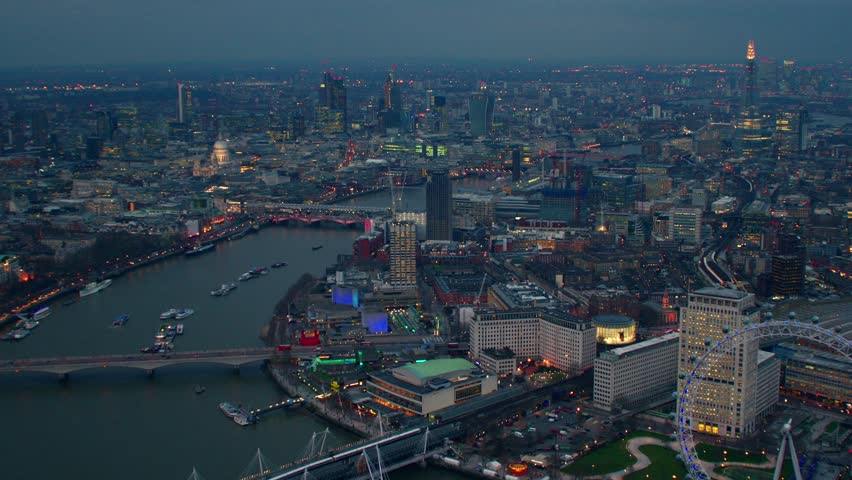 Dramatic aerial shot along the River Thames in Central London. Featuring well known landmarks including The London Eye, The Shard, City Financial District & Waterloo Bridge.