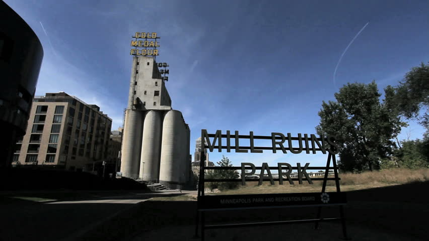 MINNEAPOLIS, MINNESOTA - CIRCA 2012: Minneapolis Mill Ruins Park sign with joggers - HD stock video clip