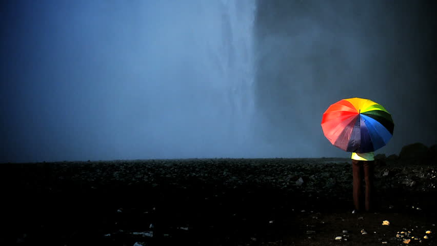 Concept shot of lone female standing on the edge of a waterfall with rainbow umbrella to shelter from changing climate conditions 60 FPS - HD stock video clip