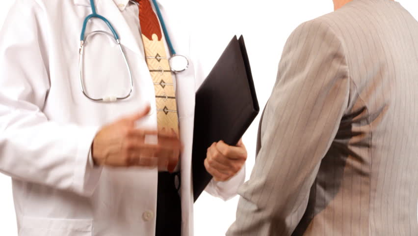 A doctor and a businesswoman or patient who appear to be finishing a discussion, shake hands.