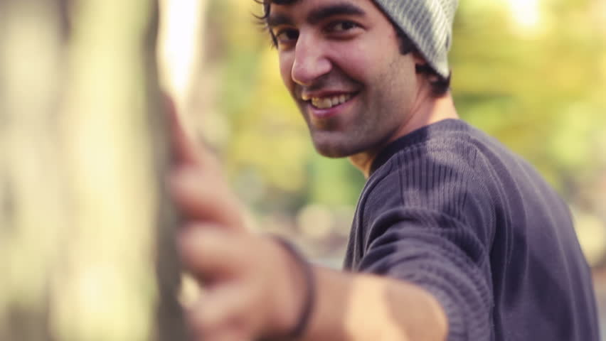 A series of shots of a man and woman walking around a tree and smiling and flirting with each other. Close up shot