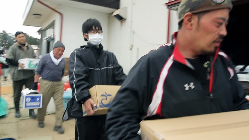 JAPAN - April 2011: Japanese survivors and relief workers bring supplies to a shelter