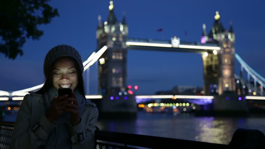 Smartphone woman on cell phone in London in front of Tower Bridge at night. Girl using app or texting sending sms text message with mobile phone by the River Thames, London, England, Great Britain.