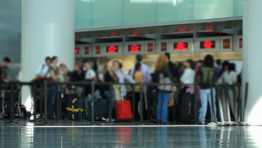 Airport travelers waiting in line at check-in area.