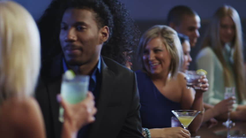 People have conversations while hanging out at the bar in a night club - HD stock video clip