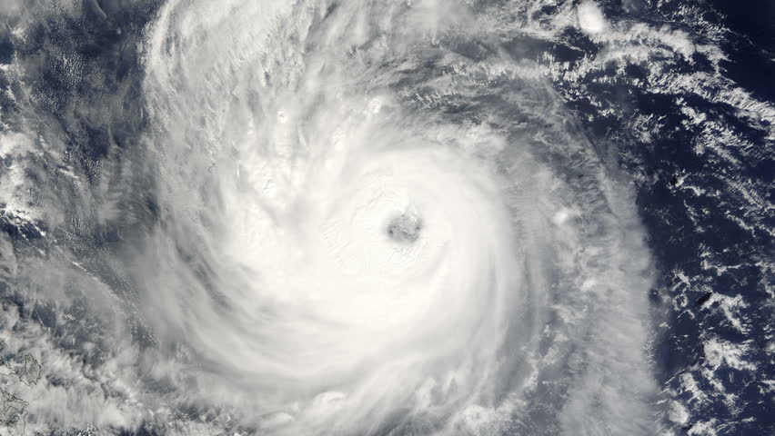 Descent into the well defined eye of a large typhoon / hurricane as it churns in the ocean.