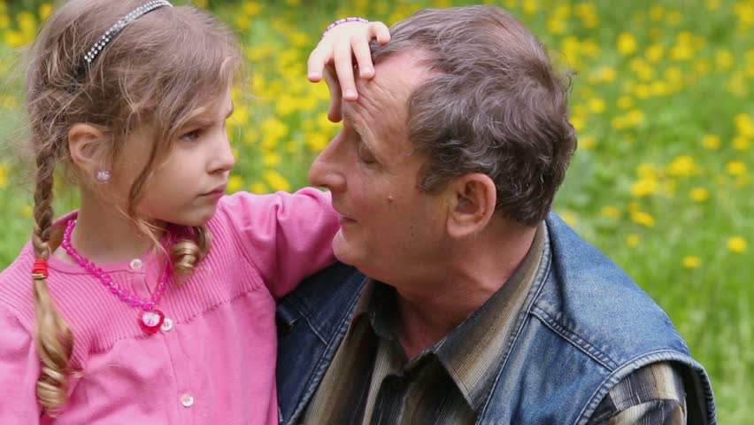 Grandfather talks with granddaughter which smiles on dandelion lawn at sunny day