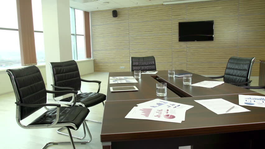 The interior view of a contemporary business office with financial documents lying on the table