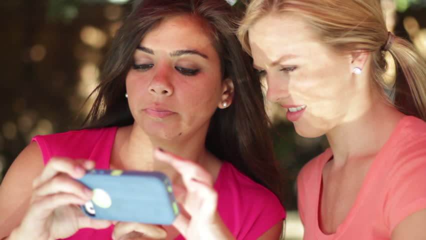 Beautiful young women looking at things on the screen of a smart phone.  Two shot, close up, outdoors on a summer's day.