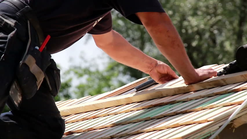 Roofers installing roof tiles on the roof. Roofer is about to nail in the roof tile that he has just placed on the roof. - HD stock footage clip