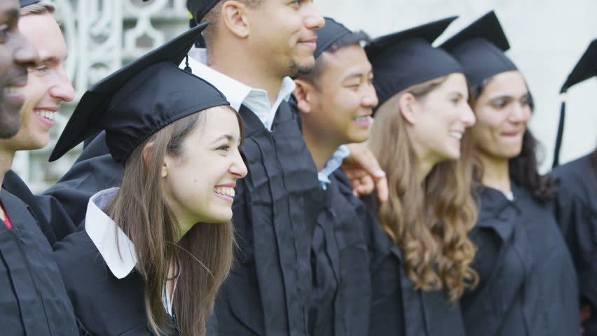 Happy and excited group of student friends on graduation day standing in a line outdoors and posing for photographs. One female graduate turns towards the camera and smiles.  - HD stock footage clip