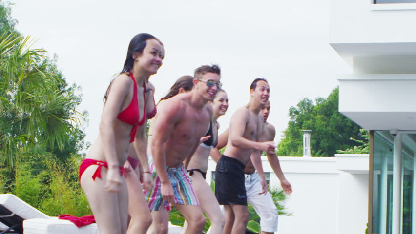Excited group of young friends jumping into swimming pool on a summers day. In slow motion. - HD stock video clip