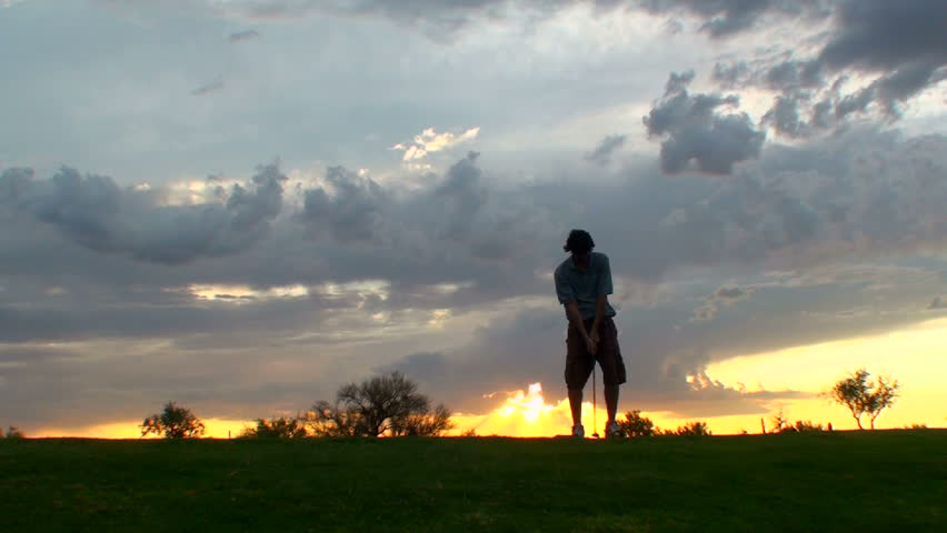Young man hits golf ball at sunset. 1920x1080 - HD stock footage clip