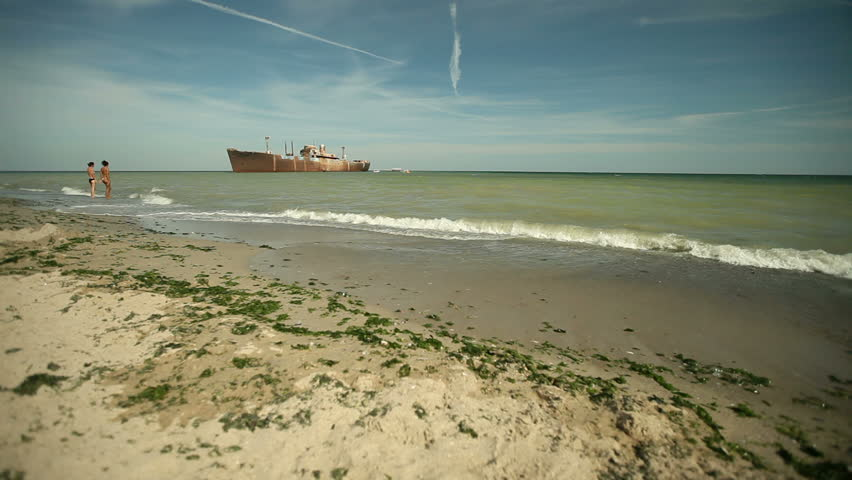 Sea waves wash beach sand. Shipwreck in background. Low wide angle view. - HD stock video clip
