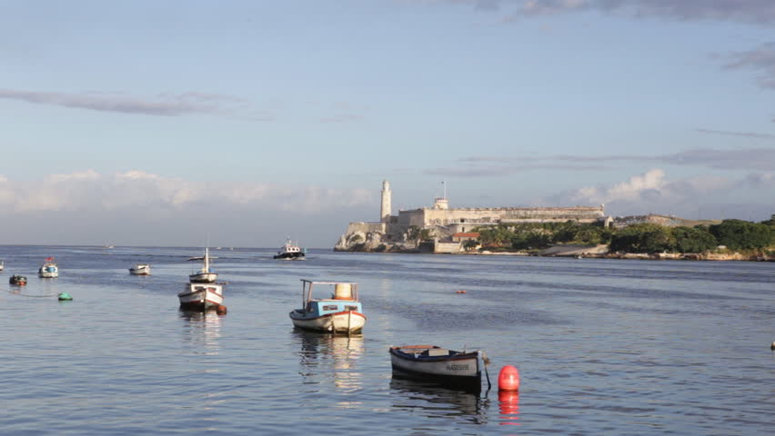 HAVANA-NOVEMBER 6:Small fishing boats at the bay with El Morro in the background on November 6, 2013 in Havana.With over 2 million inhabitants, Havana is and the largest city in the caribbean area - HD stock video clip