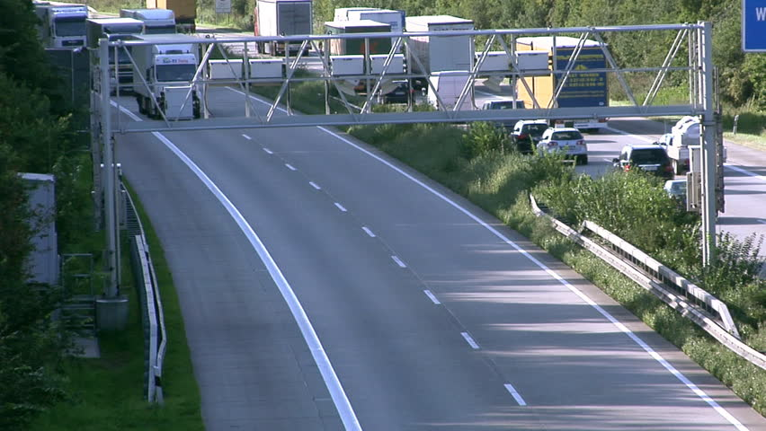 Lots of trucks passing under a toll collecting device on a German Autobahn (motorway).  - HD stock footage clip