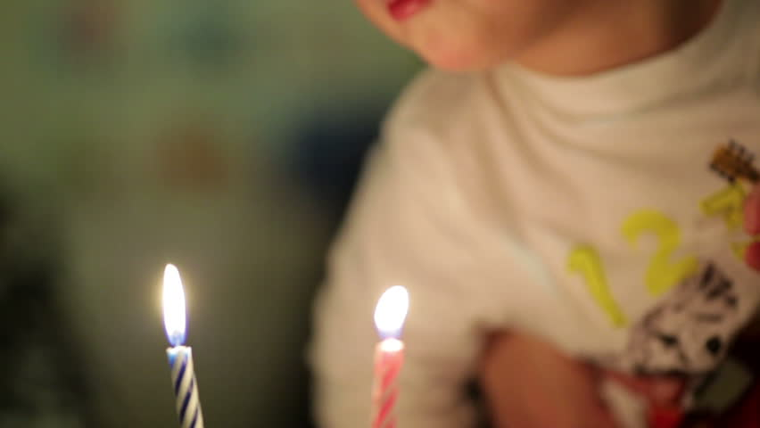 Little boy blowing out two candles on his birthday cake, everybody applauding, then mother taking away the candles. - HD stock footage clip