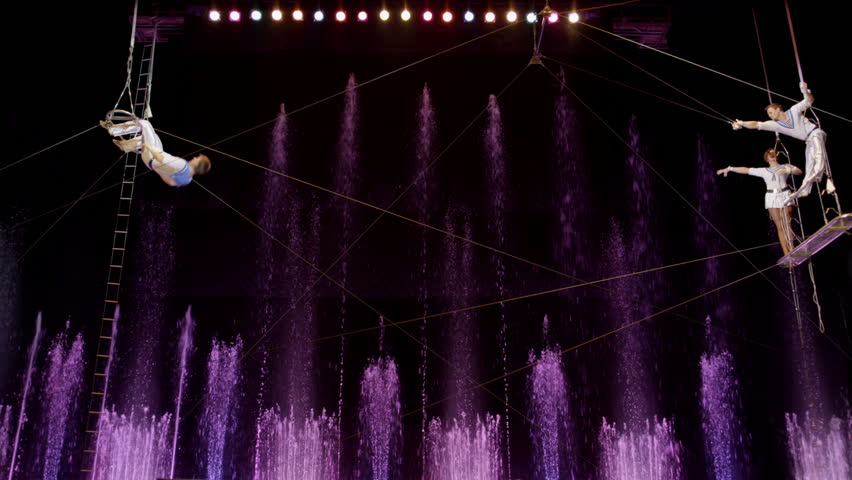 MOSCOW - NOVEMBER 6: Aerial acrobatics perfomance in Aquamarine circus. Purple fountains in background. Acrobat's fall at the end on November 6, 2013 in Moscow, Russia.