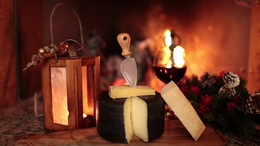 Video clip showing a typical Italian seasoned cheese and wine in front of a country fireplace during the winter holidays.
