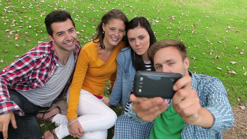 Students taking a selfie on the grass on college campus