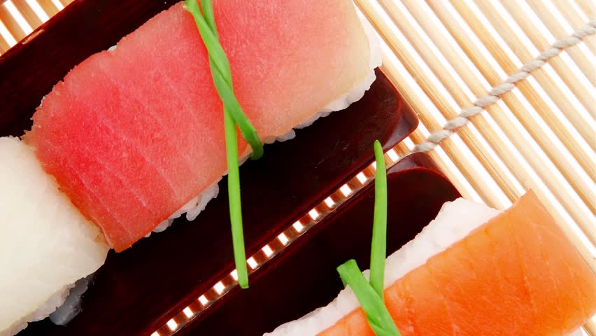 Japanese Cuisine - Set of Tuna (maguro) Salmon (sake) and Eel (unagi) Nigiri Sushi with Wasabi and Ginger on bamboo mat 1920x1080 intro motion slow hidef hd
