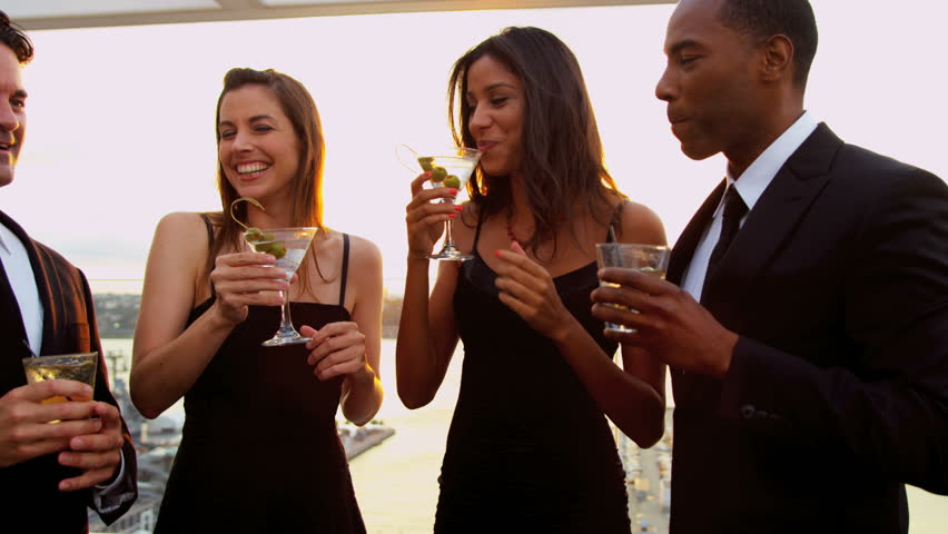 Young diverse happy male and female friends enjoying together luxury cocktail party on roof sun lens flare shot on RED EPIC, 4K, UHD, Ultra HD resolution