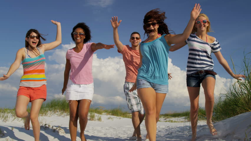 Carefree male female teenagers bright clothes enjoying weekend break together having fun on beach shot on RED EPIC, 4K, UHD, Ultra HD resolution