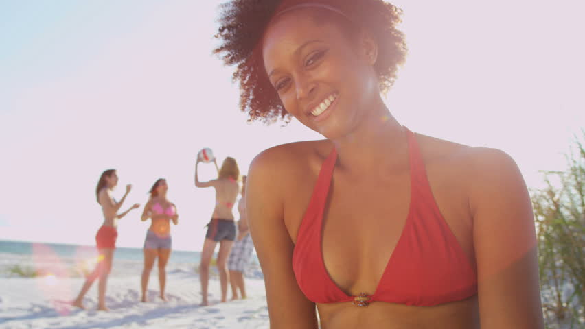 Close up pretty young African American girl smiling to camera sitting beach friends playing ball background sun lens flare shot on RED EPIC, 4K, UHD, Ultra HD resolution - 4K stock video clip