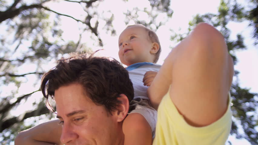 Portrait cute little male toddler laughing sitting on young fathers shoulders outing park sun lens flare head shoulders shot on RED EPIC, 4K, UHD, Ultra HD resolution - 4K stock footage clip
