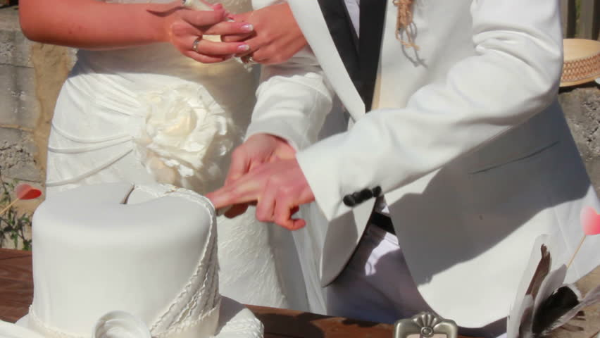 newlyweds cut the wedding cake with knife  - HD stock video clip