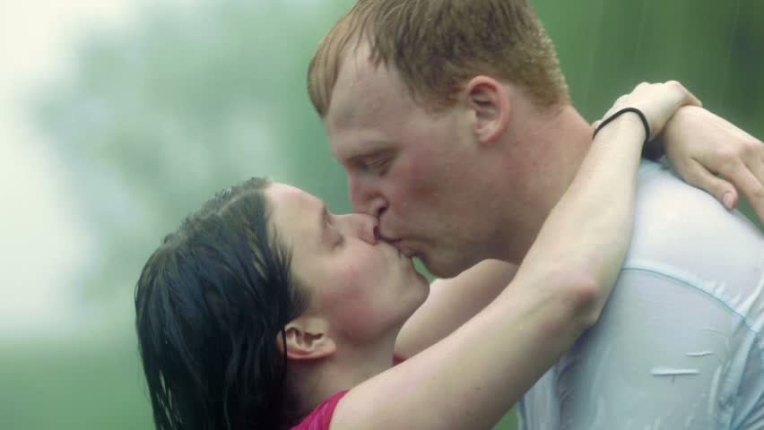 Young couple (man and woman), kissing in a heavy rain storm. Boy picks girl up and swings her in his arms before kissing her. - HD stock video clip