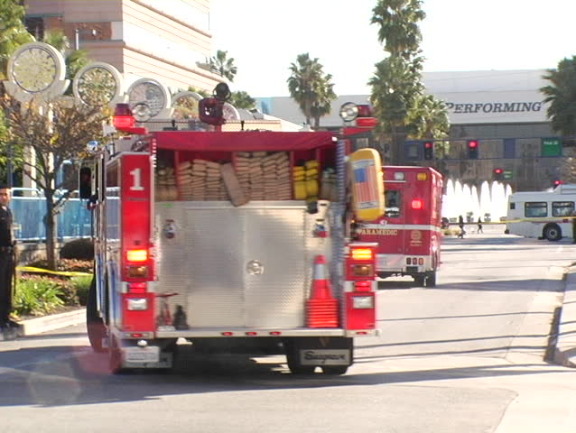 A fire engine responds to a call as a police officer seals off a crime scene with police tape. - SD stock footage clip