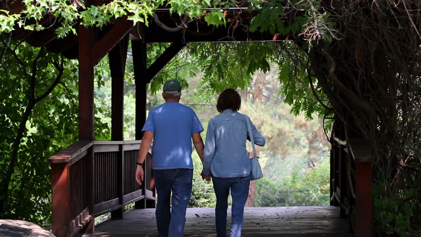 Two senior adult retirees walk across a small covered footbridge in a romantic setting. - HD stock footage clip