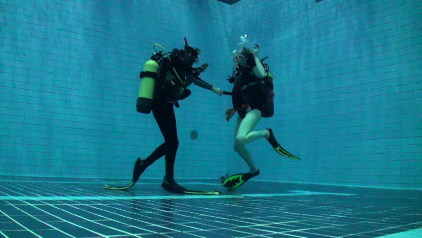Two scuba divers going up to the surface in a deep pool