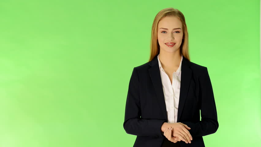 Young business woman presenting sth by a hand. On green background.
