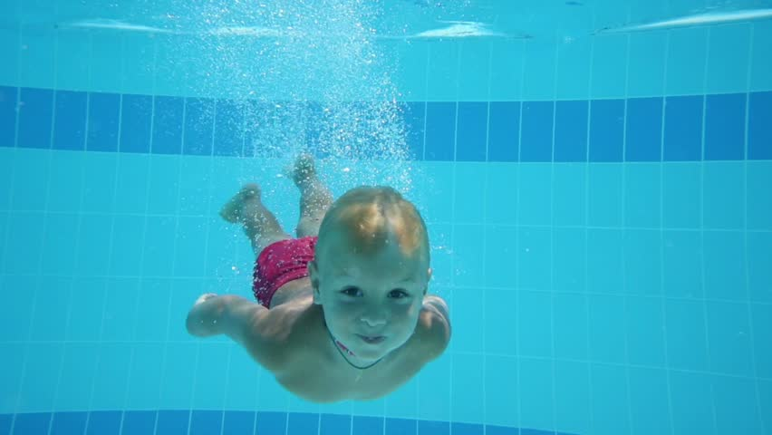 Cute little boy dives in blue pool with open eyes and floated back - HD stock footage clip