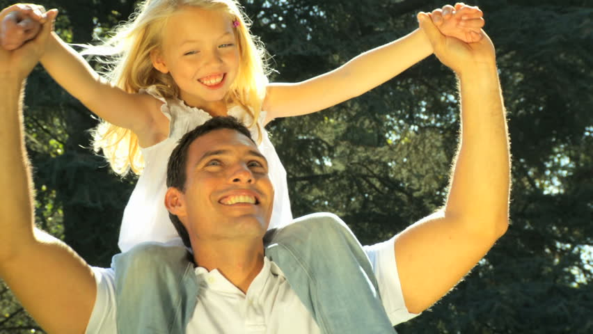 Young father laughing with his daughter on his shoulders while outdoors on a summers day
