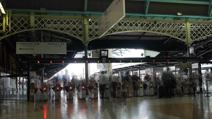 SYDNEY, AUSTRALIA - DECEMBER 23 2013: a time lapse shot of commuter passing through ticket turnstiles at a train station