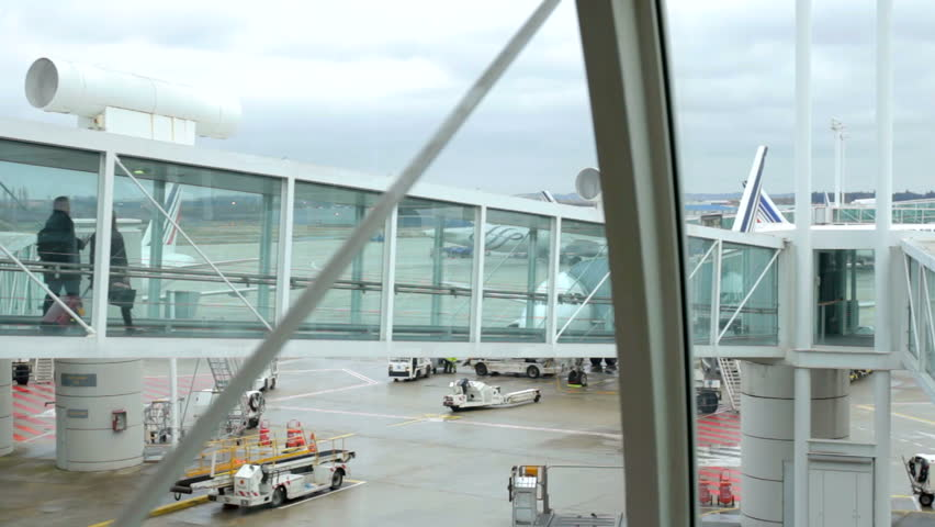 Walking jet bridge – airport terminal to airplane. Passengers boarding through the jetway and entering the airplane to take their flight.