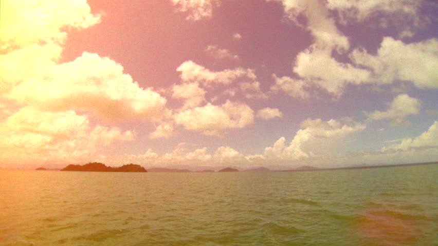 Retro, 8mm look, sailing on boat view of tropical islands.