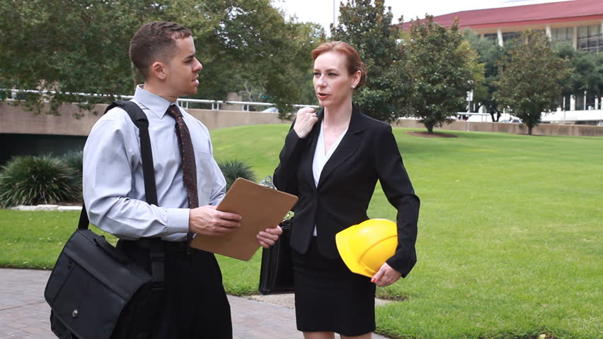A man holding a clipboard talks with a woman who is holding a hardhat. - HD stock video clip